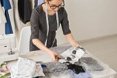 Dressmaker, Fashion Designer And Tailor Concept - Beautiful Young Stylist At Workplace Near Rack Wit poster