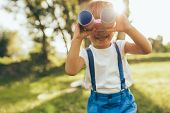 Outdoors Closeup Portrait Of Little Boy Playing With A Binoculars Searching For An Imagination Or Ex poster