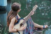 Beautiful Hippie Girl Playing Guitar Near Forest Lake poster