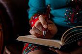Front View Of Womans Hands Writing Useful Information In Notepad.girls Hand With A Red Pen Writes Th poster