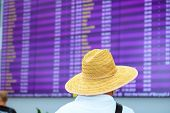 A Man In A Straw Hat Is Standing Near A Blurred Information Board For Arrivals And Departures. Infor poster