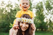 Mother Giving Piggyback Ride To Her Loving Daughter Outside In Nature. Hippie Mother And Happy Baby  poster