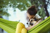Young Woman In Green Hammock With Cute Dog Welsh Corgi In A Park Outdoors. Beautiful Happy Female In poster
