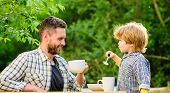 Dad And Cute Toddler Boy Having Lunch Outdoors. Child Care. Feeding Son Natural Foods. Feed In Right poster