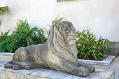 The Sculpture Of The Stone Lion On The Pedestal. Sculpture Near The Building. poster