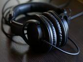 Black Studio Headphones On A Black Wooden Table. Sound Designers Headphones poster