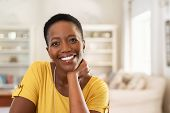 Portrait of mature woman sitting at home and looking at camera. Cheerful black girl with short hair  poster