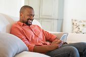 Happy black man using smart phone while relaxing at home. Smiling mature man at home sitting on couc poster