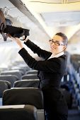 image of carry-on luggage  - pretty businesswoman putting her luggage into overhead locker on airplane - JPG