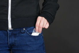 pic of methadone  - Female hand retrieving drug packet our of her blue jean pocket with copy space on black - JPG