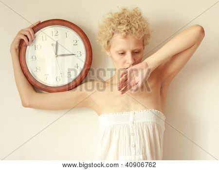 The sleepy. Young scrawny girl with big clock in hands.