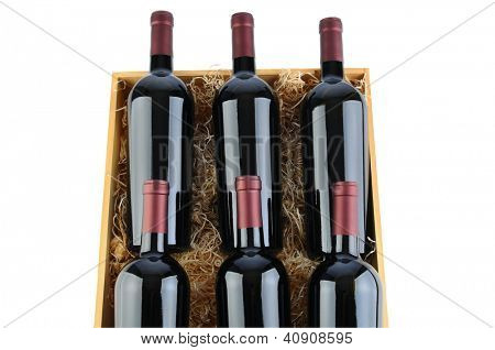 Closeup of six Cabernet Sauvignon wine bottles in a wooden crate with packing straw. Horizontal format isolated on white.