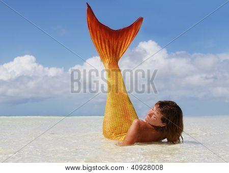 beautiful mermaid lying in the tropical sea