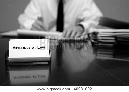Attorney at Law sitting at desk holding pen with files with business card