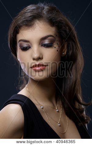 Closeup portrait of beautiful woman in glamorous makeup with strasses.