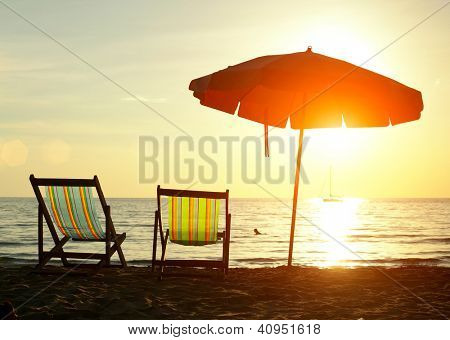 Pair of beach loungers on the deserted coast sea at sunrise.