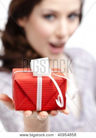 Young woman shows a present wrapped in red paper, isolated on white
