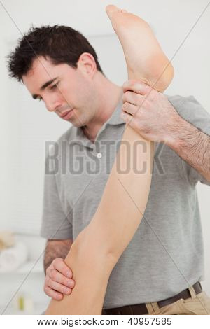 Chiropractor extending the leg of a patient in a room