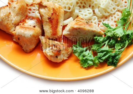 Pieces Of Fried Chicken, Pasta And Parsley On Orange Plate