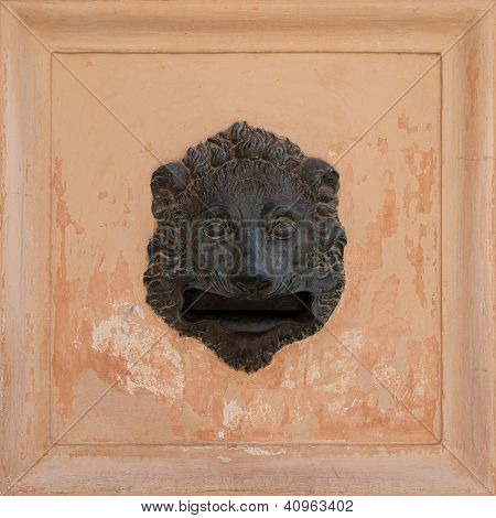 Decorative Lion head ironwork postbox set in the wall of a building in Alhambra, Spain