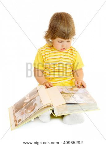 Small girl browsing an family album (faces on the photos in the album cannot be recognized)