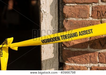 Yellow ribbon with Dutch text forbidden asbestos