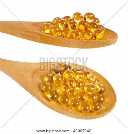 Oil pills on wooden spoons isolated on white background