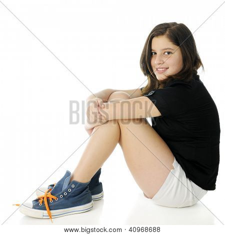 A pretty preteen looking at the viewer as she sits on the floor hugging her knees.  She's wearing over-sized high-top sneakers with bright laces.  On a white background.