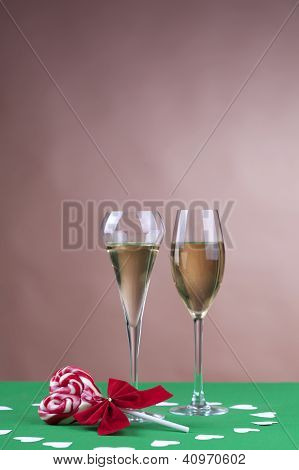 Two Glases Of Champagne Next To A Heart Shape Candy