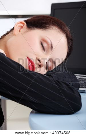 Attractive tired businesswoman sleeping at the desk.