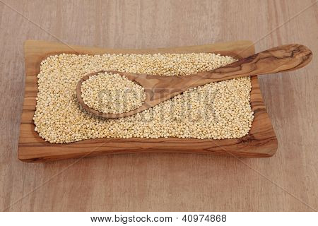 Quinoa grain in an olive wood bowl and spoon over papyrus background.