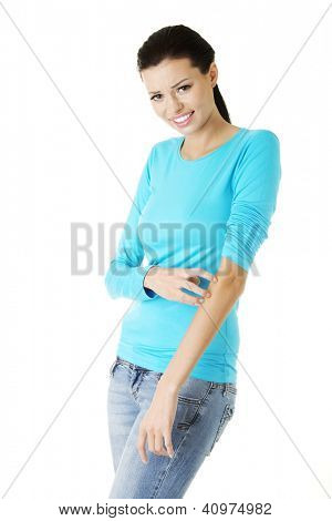 Young beautiful woman scratching her self. Isolated on white