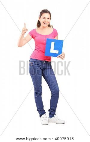 Full length portrait of a happy teenager holding L plate and giving a thumb up isolated against white background