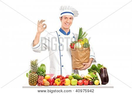 Male chef holding a bag with healthy ingridients behing a table full of various vegetables and fruits