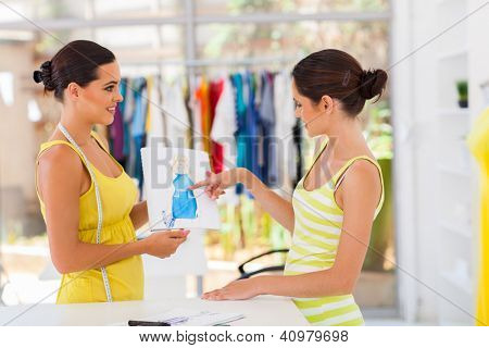 pretty fashion designer showing design to her client
