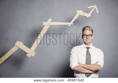 Concept: Positive business outlook. Smiling confident businessman in front of business graph with upward trend, isolated on grey background.
