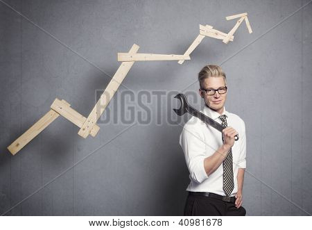 Concept: Building your own successful career or business. Smiling confident businessman holding  wrench in front of business graph with positive trend, isolated on grey background.