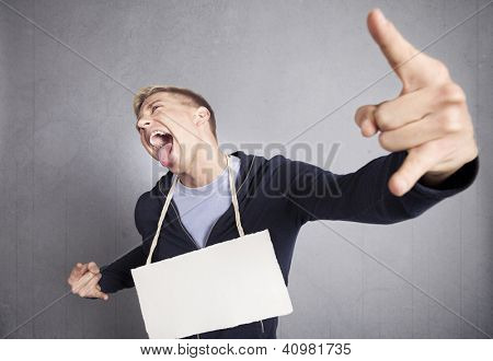 Nasty provocative man holding white empty signboard with space for text isolated on grey background.