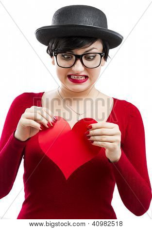 Beautiful and funny nerd girl ripping a paper heart,  isolated on white background