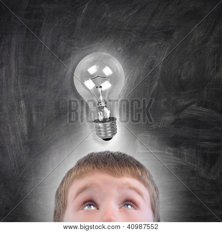 Boy With Light Bulb Idea Looking Up