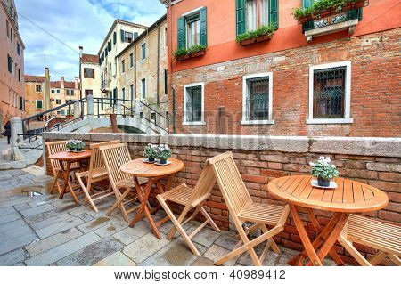 Wooden tables on narrow street among typical colorful houses and small bridge in Venice, Italy.