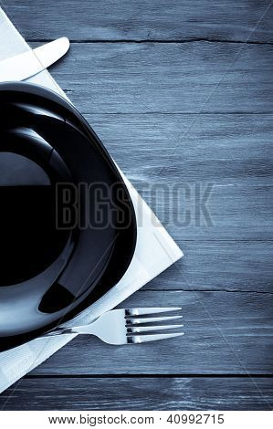plate, knife and fork at napkin on wooden background