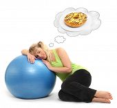 Funny picture of a hungry overweight woman dreaming on the ball. Weight loss concept.