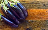 pic of aubergines  - Fresh organic aubergines on rustic wooden table - JPG