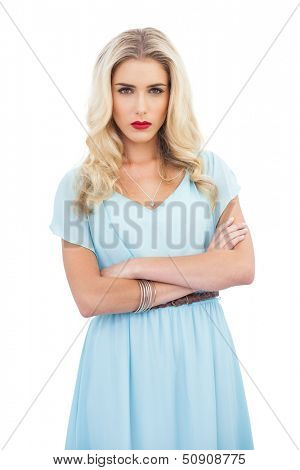 Severe blonde model in blue dress posing crossed arms on white background