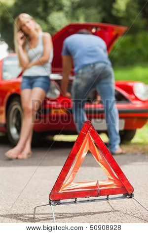 Close up on triangle warning sign with broken down car on background