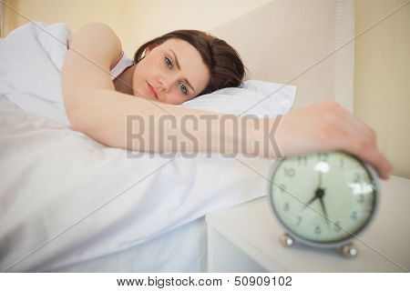 Sleepy brunette turning off her alarm clock in her bedroom