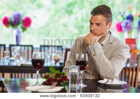 Handsome man waiting for his girlfriend with a bouquet in a classy restaurant