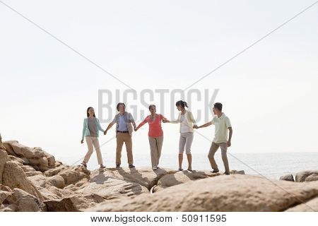 Multi-generational family holding hands on rocks by the sea