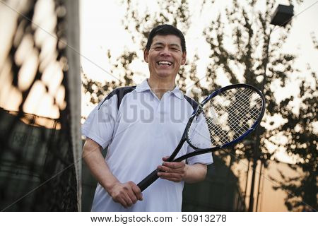 Senior men playing tennis, portrait